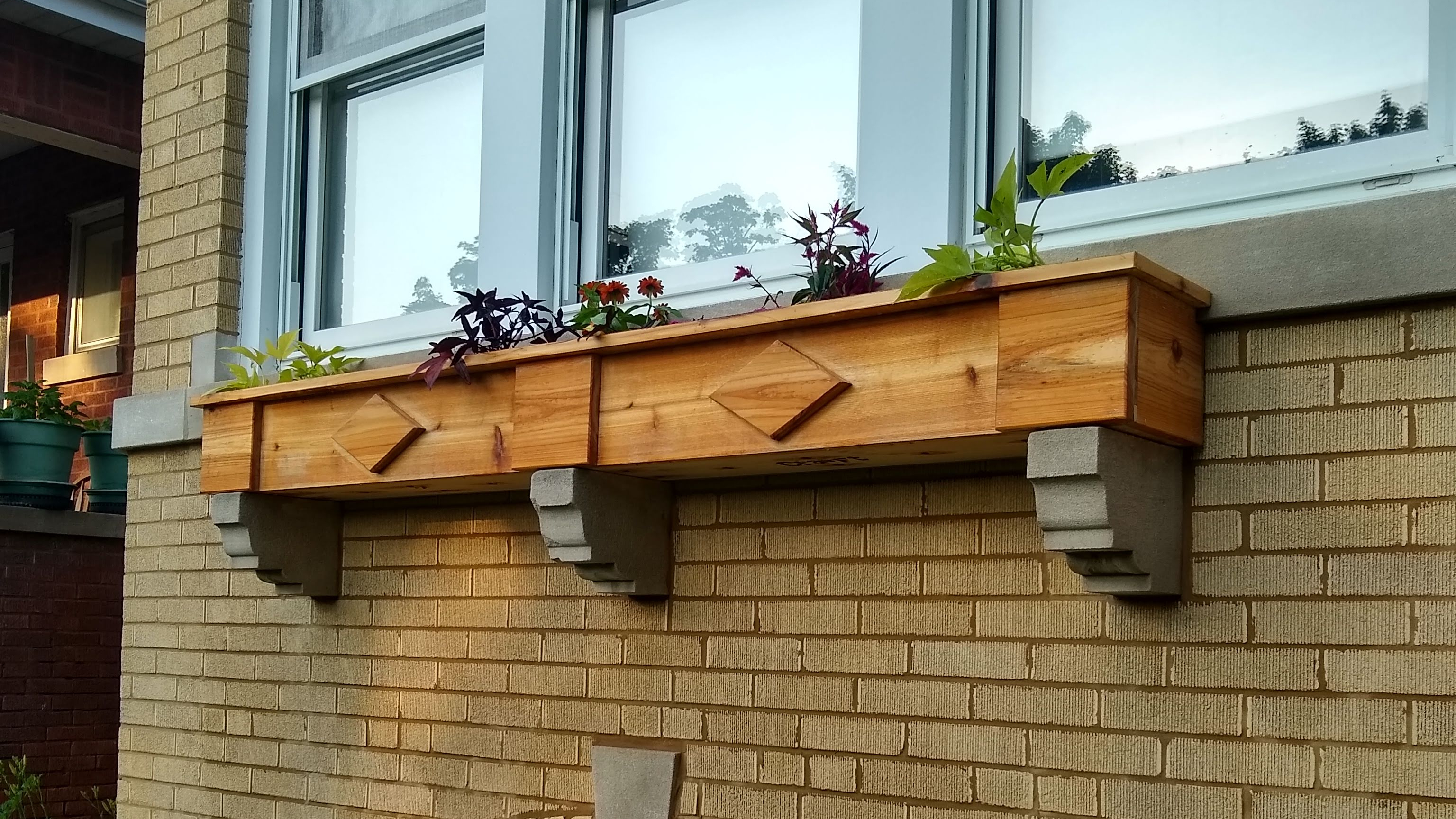 A cedar window box resting on limestone corbels protuding from the front of a brick bungalow.