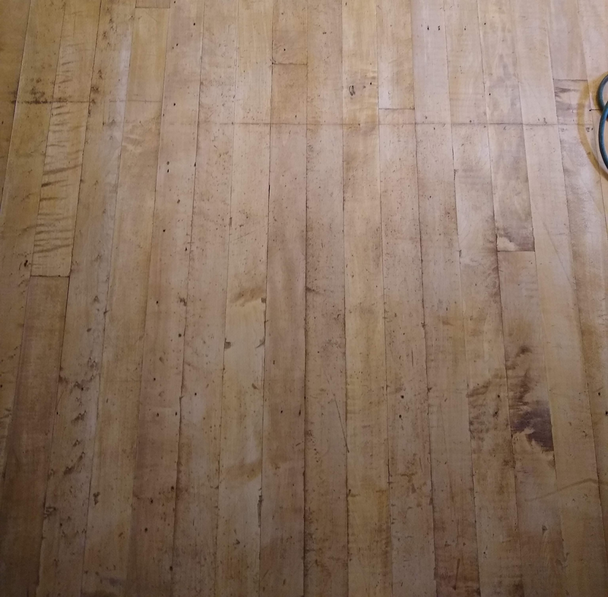 An image of 100 year old maple floorboards with no finish.